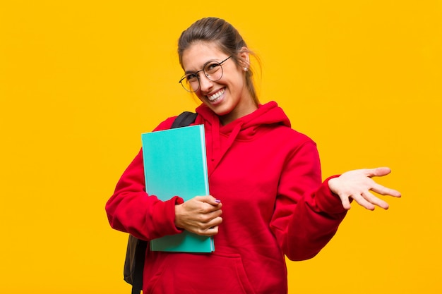 Jeune jolie étudiante se sentant heureuse, étonnée, chanceuse et surprise, comme si elle disait sérieusement