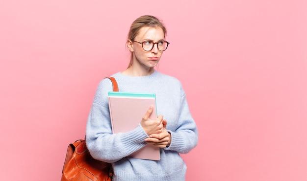 Jeune jolie étudiante se sentant triste, contrariée ou en colère et regardant de côté avec une attitude négative, fronçant les sourcils en désaccord