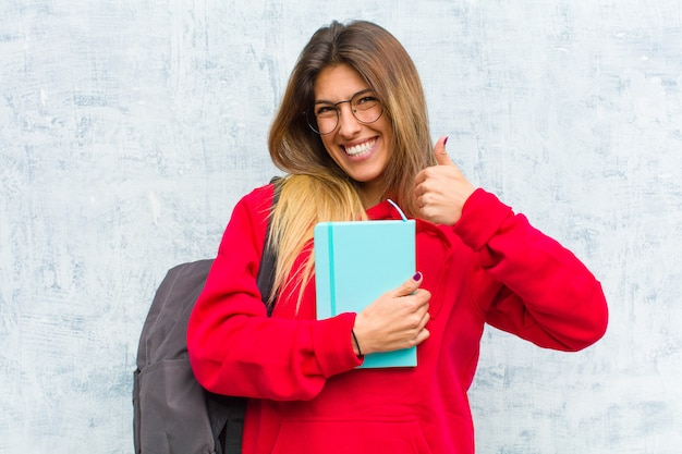 Jeune jolie étudiante souriante ayant l'air largement heureuse, positive, confiante et prospère, avec les deux pouces
