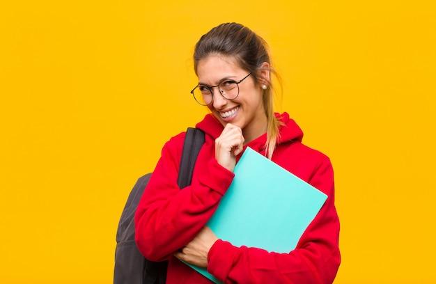 Jeune jolie étudiante souriante, profite de la vie, heureuse, amicale, satisfaite et insouciante avec la main sur le menton
