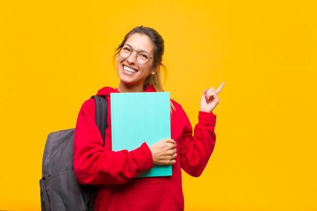 Jeune jolie étudiante sourit avec bonheur et pointe du côté et vers le haut, les deux mains montrant un objet dans l'espace de copie