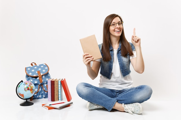 Jeune jolie étudiante en vêtements en denim tenant un livre pointant l'index vers le haut assis près du globe, sac à dos, livres scolaires isolés