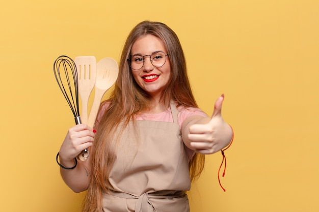 Jeune jolie femme abandonnant le pouce et tenant des ustensiles de cuisine