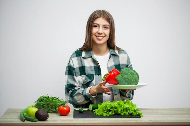 Jeune jolie femme adhère au régime alimentaire et détient une assiette de légumes