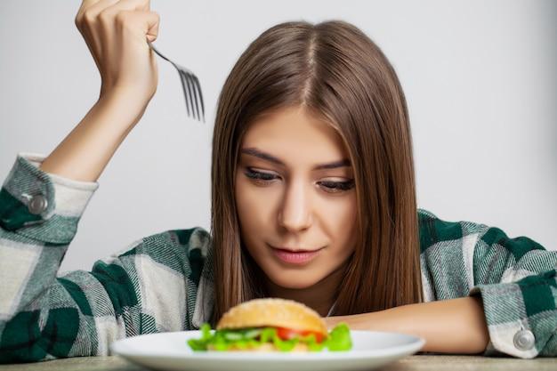 Jeune jolie femme adhère au régime alimentaire mais choisit des aliments malsains