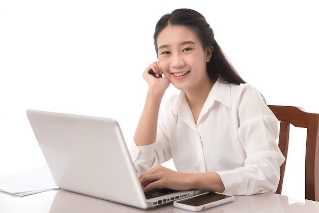 Jeune jolie femme d'affaires asiatique heureuse et souriante avec ordinateur portable au bureau sur fond blanc.