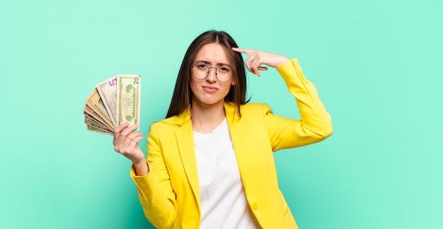 Jeune jolie femme d'affaires avec des billets en dollars