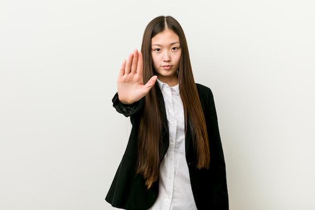Jeune jolie femme d'affaires chinoise debout avec la main tendue montrant le panneau d'arrêt, vous empêchant.