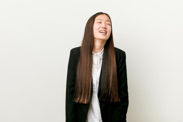 Jeune Et Jolie Femme D'affaires Chinoise Détendue Et Heureuse Rire, Cou Tendu Montrant Les Dents. Photo Premium
