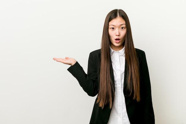 Jeune jolie femme d'affaires chinoise impressionné tenant sur la paume.