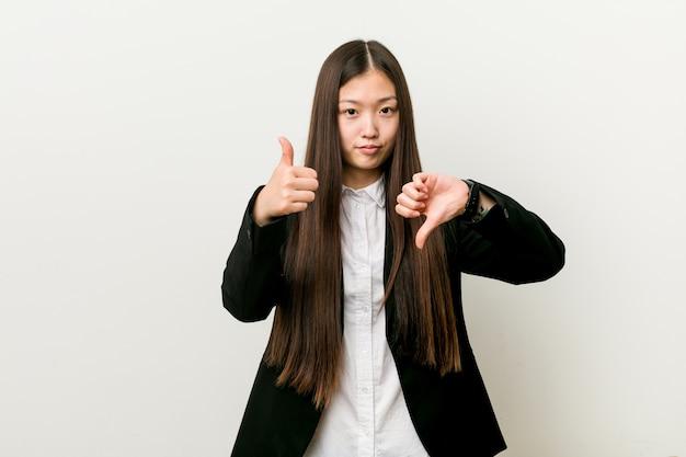 Jeune jolie femme d'affaires chinoise montrant les pouces vers le haut et les pouces vers le bas, difficile de choisir le concept