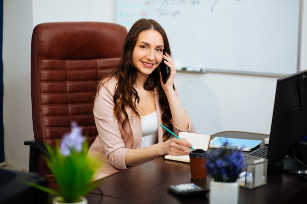 Jeune jolie femme d'affaires avec ordinateur portable au bureau
