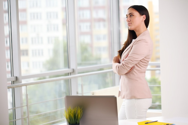 Jeune jolie femme d'affaires avec ordinateur portable au bureau.