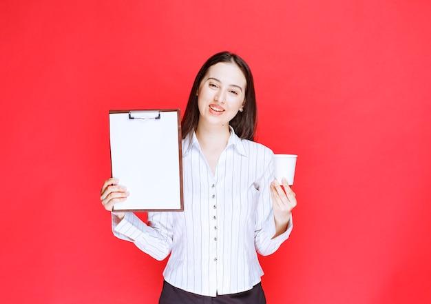 Jeune jolie femme d'affaires posant avec un presse-papiers vide et une tasse en plastique.
