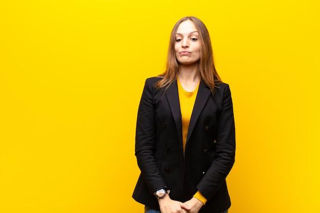 Jeune jolie femme d'affaires à la recherche dingue et drôle avec une sournoise expression, plaisantant et rigolant sur un fond orange