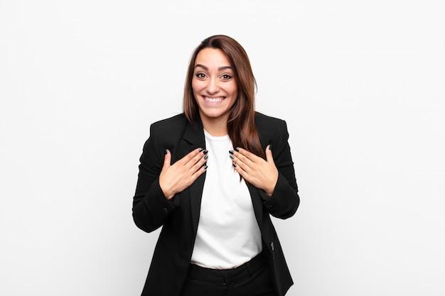 Jeune jolie femme d'affaires à la recherche de plaisir, surpris, fier et excité, pointant vers soi contre le mur blanc