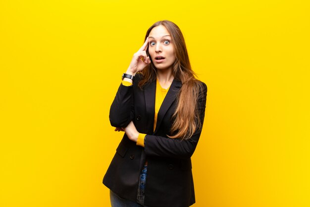 Jeune jolie femme d'affaires à la recherche de surprise, bouche bée, choquée, réalisant une nouvelle pensée, idée ou concept