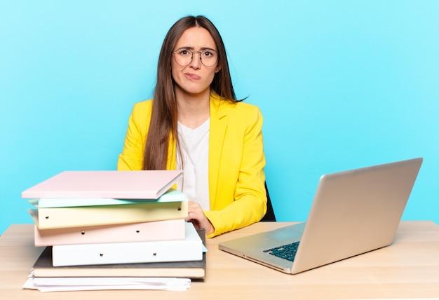 Jeune jolie femme d'affaires se sentant confuse et douteuse, se demandant ou essayant de choisir ou de prendre une décision