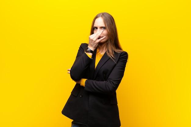Jeune jolie femme d'affaires se sentant dégoûté, tenant le nez pour éviter de sentir une odeur nauséabonde et désagréable contre le mur orange