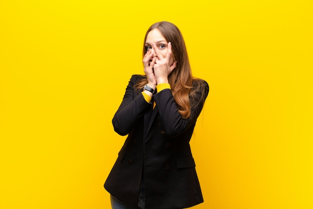 Jeune jolie femme d'affaires se sentant effrayée ou embarrassée, jetant un coup d'œil ou espionnant, les yeux à demi couverts de mains contre le mur orange