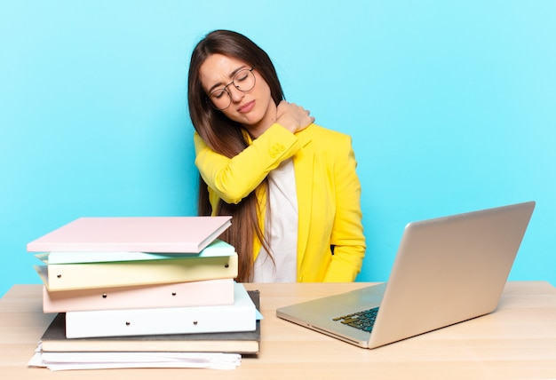 Jeune jolie femme d'affaires se sentant fatiguée, stressée, anxieuse, frustrée et déprimée, souffrant de douleurs au dos ou au cou