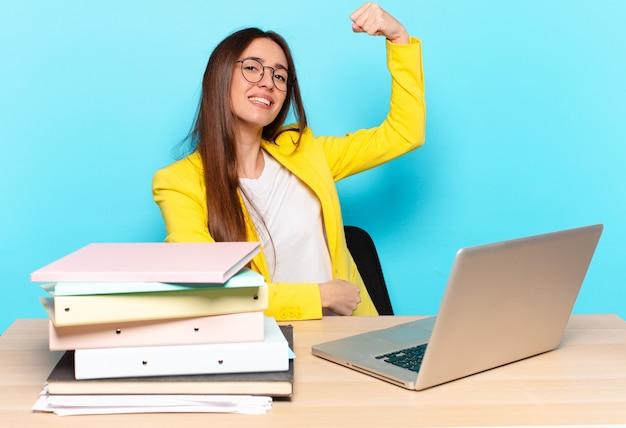 Jeune jolie femme d'affaires se sentant heureuse, satisfaite et puissante, ajustement flexible et biceps musclés, ayant l'air fort après la salle de gym