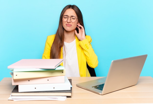 Jeune jolie femme d'affaires se sentant stressée, frustrée et fatiguée, se frottant le cou douloureux, avec un regard inquiet et troublé