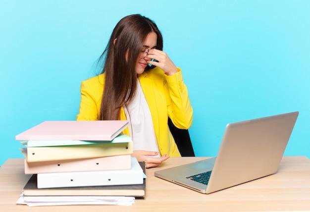 Jeune jolie femme d'affaires se sentant stressée, malheureuse et frustrée, touchant le front et souffrant de migraine de maux de tête sévères
