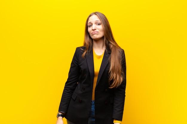 Jeune jolie femme d'affaires se sentant triste et souriante avec un regard malheureux, pleurant avec une attitude négative et frustrée contre orange