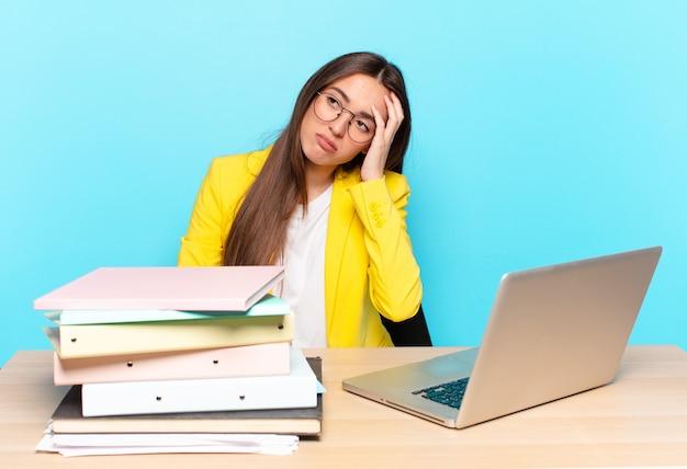 Jeune jolie femme d'affaires se sentir ennuyé, frustré et somnolent après une tâche ennuyeuse, terne et fastidieuse, tenant le visage avec la main