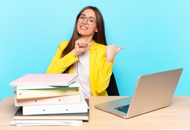 Jeune jolie femme d'affaires souriant gaiement et pointant avec désinvolture pour copier l'espace sur le côté, se sentir heureux et satisfait