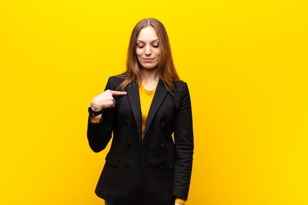 Jeune jolie femme d'affaires souriant avec gaieté et désinvolture, regardant vers le bas et montrant la poitrine contre l'orange