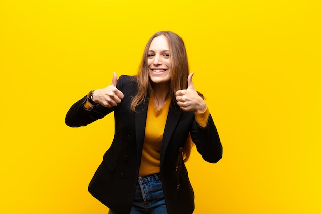 Jeune jolie femme d'affaires souriante ayant l'air largement heureuse, positive, confiante et prospère, les deux pouces contre le mur orange