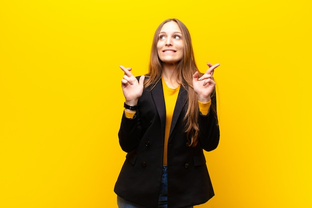 Jeune jolie femme d'affaires souriante et croisant les deux doigts avec anxiété, inquiète et souhaitant ou souhaitant bonne chance sur fond orange