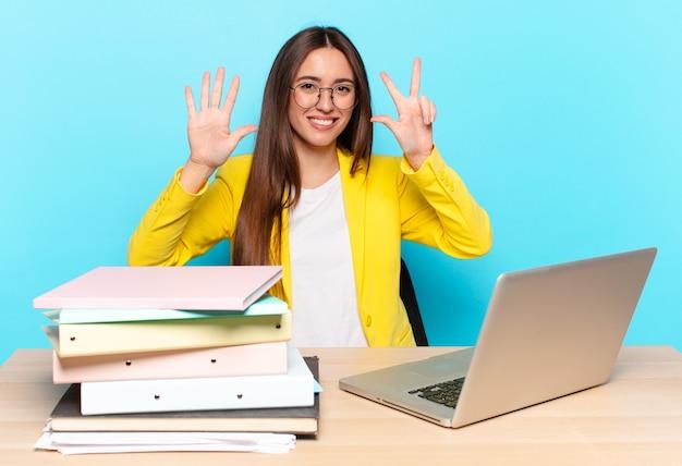 Jeune jolie femme d'affaires souriante et semblant amicale, montrant le numéro huit ou huitième avec la main vers l'avant, compte à rebours