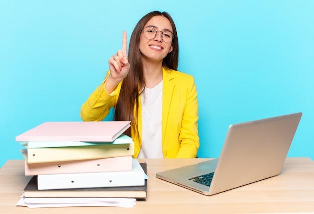 Jeune jolie femme d'affaires souriante et semblant amicale, montrant le numéro un ou le premier avec la main en avant, comptant à rebours