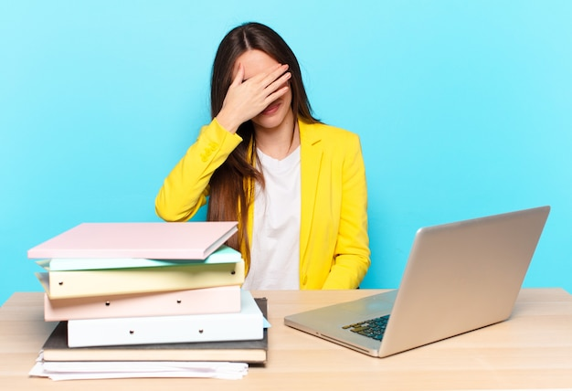 Jeune jolie femme d'affaires stressée, honteuse ou contrariée, avec un mal de tête
