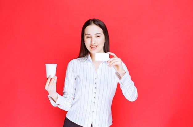 Jeune jolie femme d'affaires tenant une tasse en plastique et une carte de visite sur fond rouge.