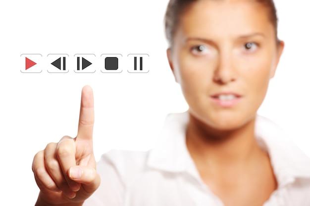 Une jeune jolie femme d'affaires touchant le bouton sur fond blanc
