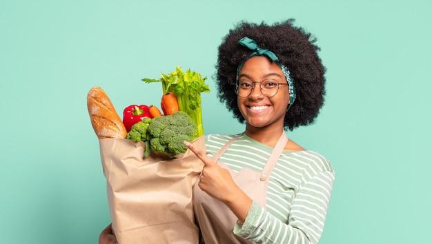 Jeune jolie femme afro à l'air arrogante, réussie, positive et fière, se montrant elle-même et tenant un sac de légumes
