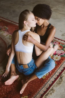 Jeune jolie femme afro-américaine et belle femme aux cheveux blonds assis sur un tapis vintage tout en passant du temps ensemble à la maison