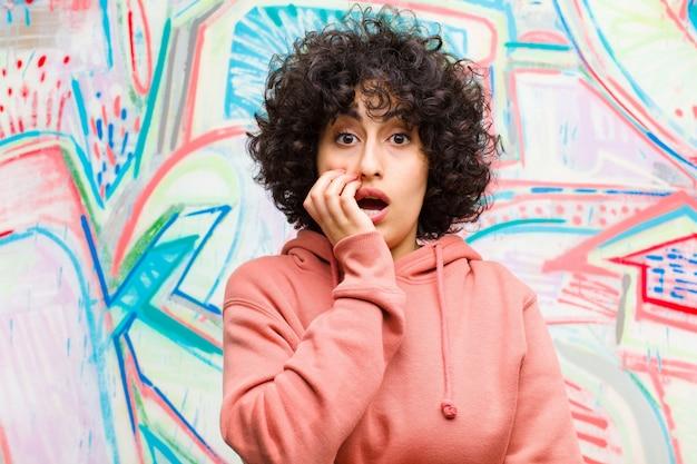 Jeune jolie femme afro bouche bée sous le choc et l'incrédulité, la main sur la joue et les bras croisés, se sentant stupéfaite et émerveillée devant un mur de graffitis