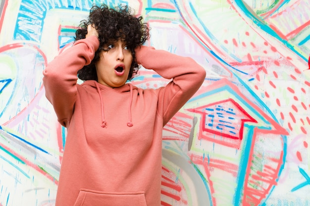 Jeune jolie femme afro avec la bouche ouverte, l'air horrifié et choqué par une terrible erreur, levant les mains pour se diriger contre le mur de graffitis
