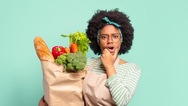 Jeune jolie femme afro avec la bouche et les yeux grands ouverts et la main sur le menton, se sentant désagréablement choquée, disant quoi ou wow et tenant un sac de légumes