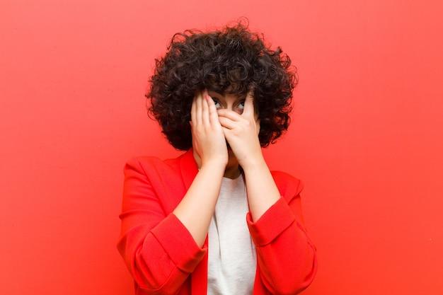 Jeune jolie femme afro couvrant le visage avec les mains