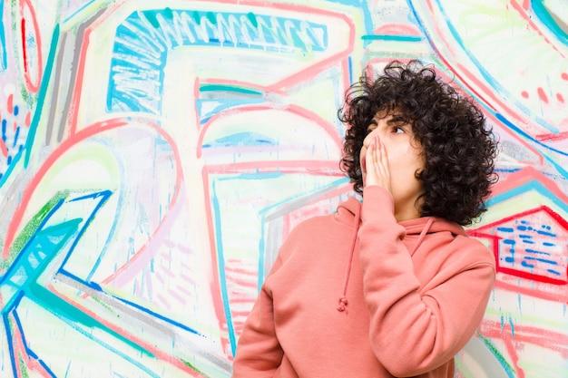 Jeune jolie femme afro criant fort et avec colère pour copier de l'espace sur le côté, avec la main à côté de la bouche contre le mur de graffitis