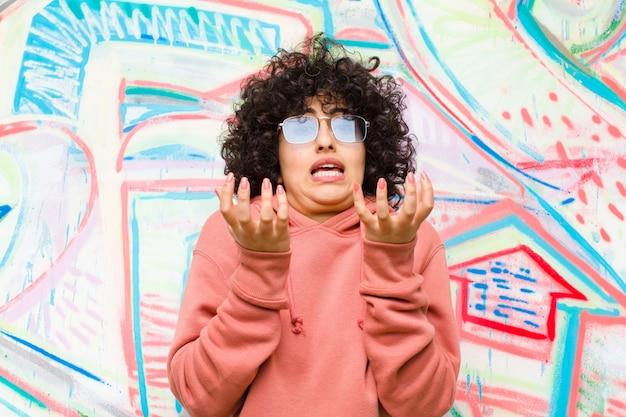 Jeune jolie femme afro désespérée et frustrée, stressée, malheureuse et agacée, criant et hurlant contre le mur de graffitis