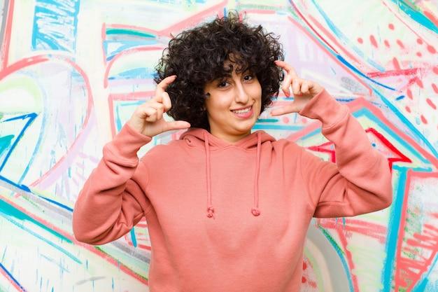 Jeune jolie femme afro encadrant ou décrivant son propre sourire à deux mains, à la recherche positive et heureuse, bien-être contre un mur de graffitis