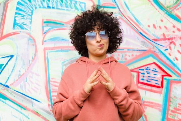 Jeune jolie femme afro intrigante et conspirante, pensant astuces et astuces sournoises, mur de graffitis rusé et trahissant