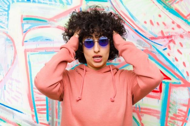 Jeune jolie femme afro levant les mains sur la tête, bouche bée, se sentant extrêmement chanceux, surpris, excité et heureux contre le mur de graffitis